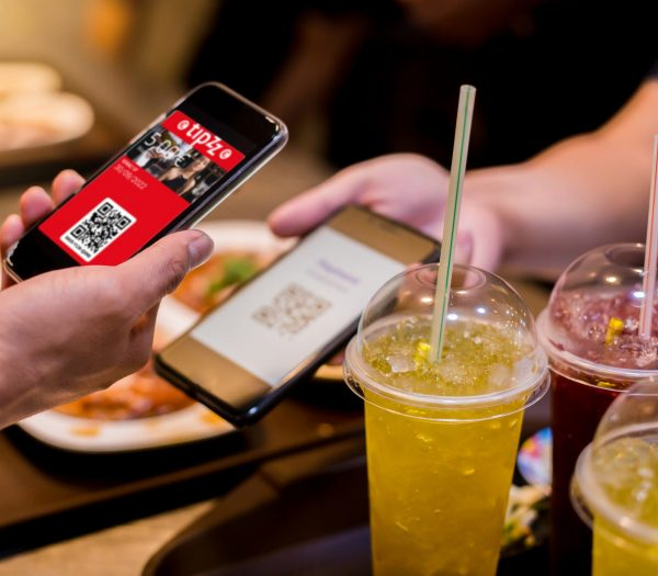 Selective focus to smart phone in hand to scan QR code tag with blurry food, dessert and customers in restaurant to accepted generate digital pay without money. Qr code payment concept.