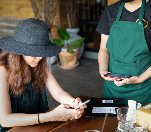 Lady customer holding phone near nfc terminal make contactless mobile payment, saleswoman on coffeeshop counter, woman client pay in cafe with cellphone via pos machine or qr code